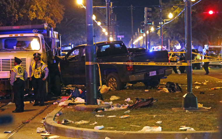 Police next to a pickup truck that slammed into a crowd and other vehicles during the Krewe of Endymion parade Saturday in New Orleans.