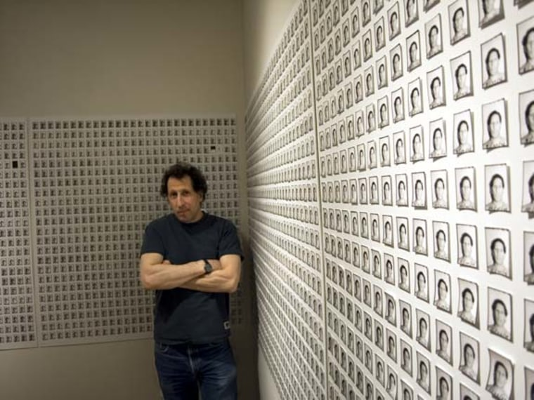 Karl Baden stands in front of an installation of his images.