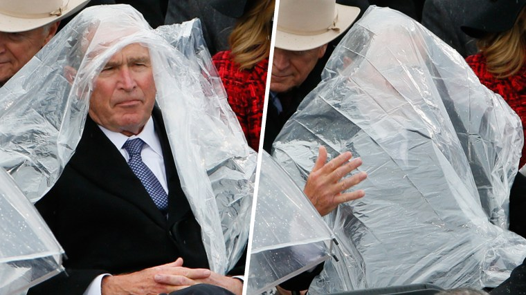 Former President George W. Bush uses a plastic sheet to deal with the rain during the inauguration ceremonies swearing in Donald Trump