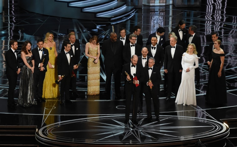 Image: Jordan Horowitz speaks while holing an oscar and the winner card before being notified about the mistake