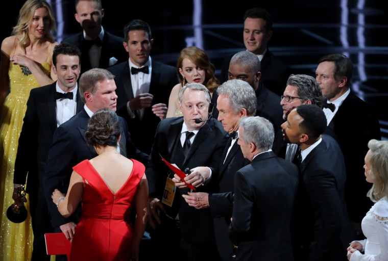Image: Warren Beatty holds the card for the best picture winner on stage during the confusion