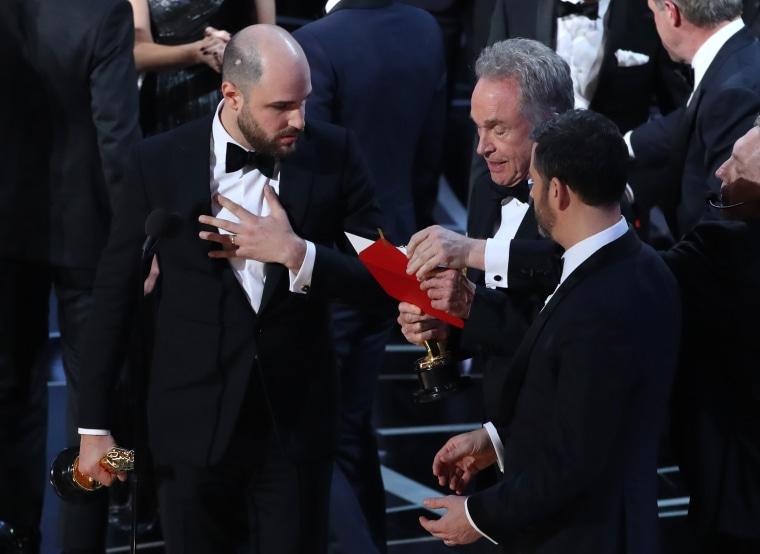 "Image: Jordan Horowitz of ""La La Land"" speaks with award presenter Warren Beatty and show host Jimmy Kimmel"