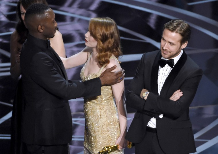 Image: Ryan Gosling, right, stands with his arms folded as Emma Stone, center, congratulates Mahershala Ali