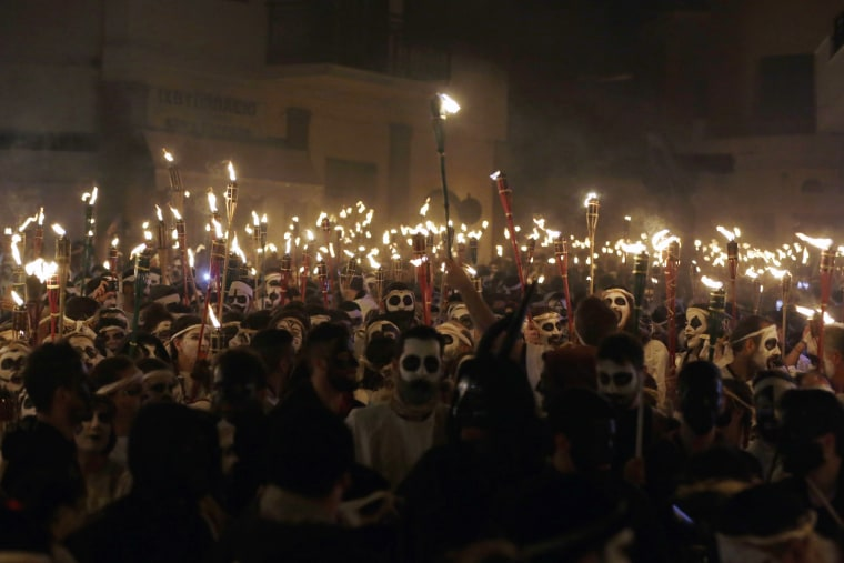 Image: Young men and women with faces painted to resemble black-and-white masks wear white sheets and hold torches on long poles take part at the Torch Parade on the Greek island of Naxos, Feb. 25, 2017.