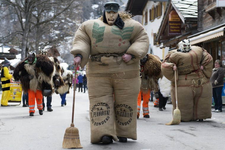 Image: 'Straw-men', wearing masks and costumes made from jute bags stuffed with straw, take part in a carnival procession in Evolene, Switzerland, Feb. 26,2017.