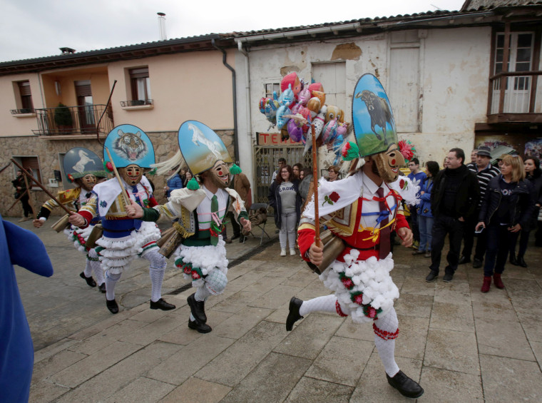 "Image: Carnival revelers dressed as ""Peliqueiros"" run along a street in the village of Laza, Spain, Feb. 26, 2017."