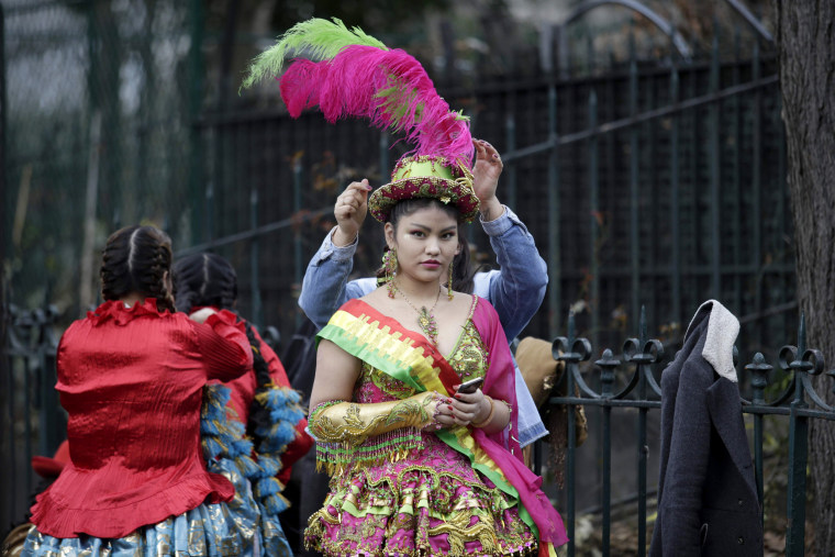 Image:A dressed up young woman is assisted in adjusting her hat at the beginning of the annual Paris' carnival on Feb. 26, 2017, in Paris.