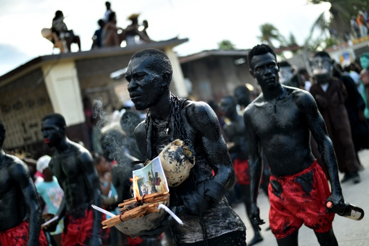 Image: A man carrying skulls walks with his band in the National Carnival Parade, in the city of Les Cayes, southwest Haiti, on Feb. 26, 2017. Their bodies are painted with a mixture of cane sugar and coal.