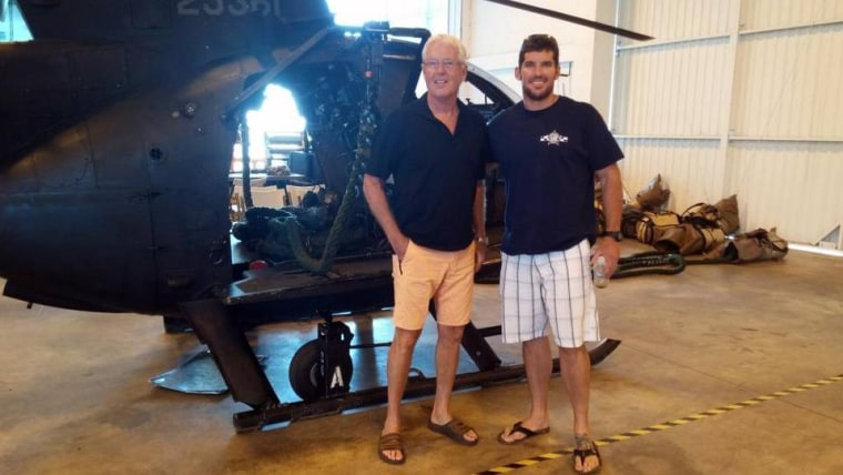 "William Owens stands with his son, William ""Ryan"" Owens, in front of a helicopter in a family photo."