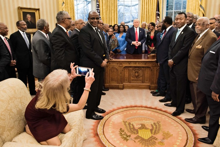 Image: Kellyanne Conway takes a photo in the Oval Office