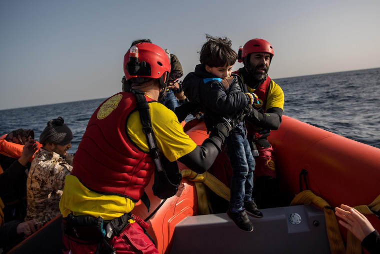 Image: A child is helped from a wooden boat