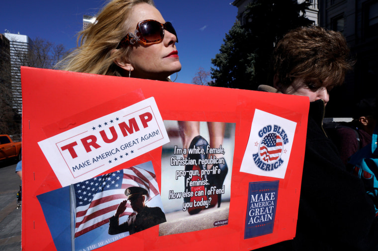 "Image: A supporter of U.S. President Donald Trump holds a sign at a ""Spirit of America"" rally in Denver"