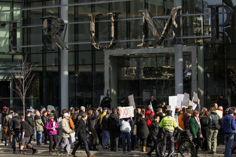 Image: Protesters hold signs outside of the Trump International Hotel and Tower during its grand opening in Vancouver