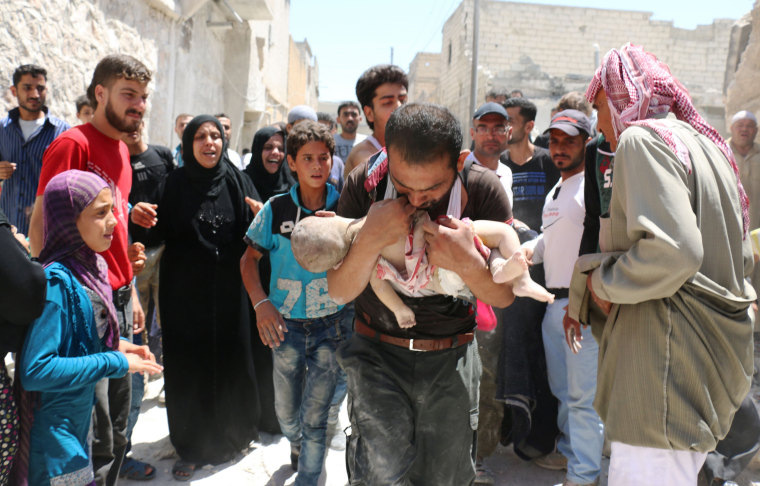 Image: A Syrian man holds the body of his child