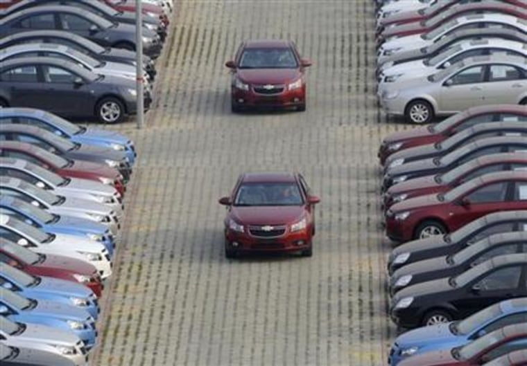 General Motors auto dealership employees drive brand new Chevrolet cars at a parking lot in Shenyang