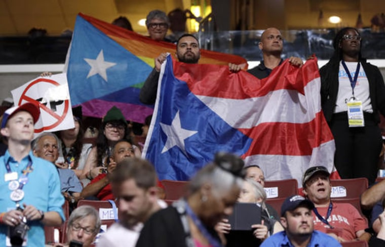 Puerto Rico delegates hold up flags during the first day of the Democratic National Convention in Philadelphia , Monday, July 25, 2016.