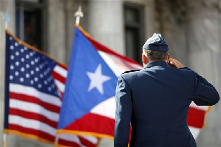 A member of the U.S. Army Honor Guard salutes the Puerto Rican and U.S. flags during the inaugural ceremony for governor-elect Alejandro Garcia Padilla, at the Capitol building in San Juan, Puerto Rico, Wednesday, Jan. 2, 2013.