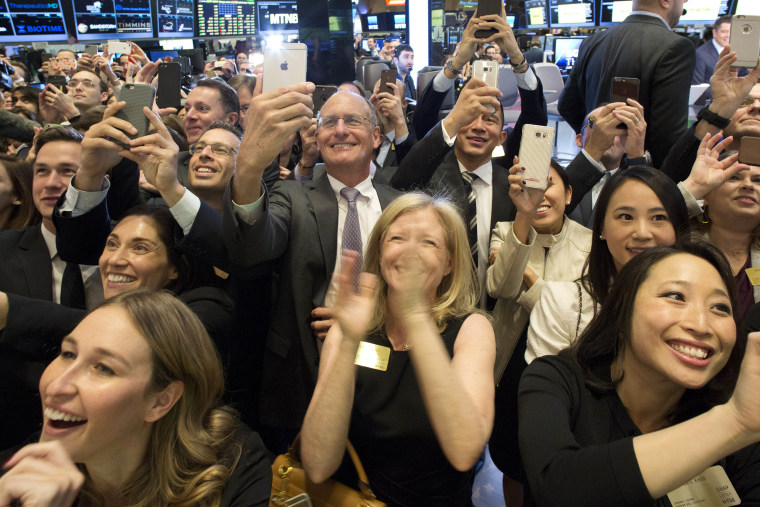 Image: Friends and employees of Snap Inc. applaud at the opening bell of the New York Stock Exchange