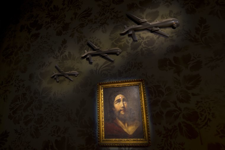 "Image: A wall decorated with models of drones and a painting of Jesus with a sniper's dot on his forehead is seen in the ""The Walled Off Hotel."""