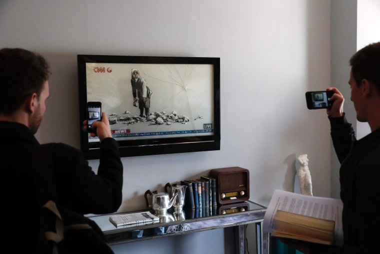 "Image: Visitors take a picture of a Bansky installation at the street artist's newly opened ""hotel."""