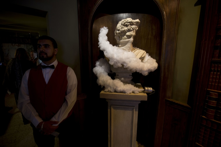 "Image: An employee stands next to a statue in the restaurant area of the The Walled Off Hotel"" in the West Bank city of Bethlehem on March 3, 2017."