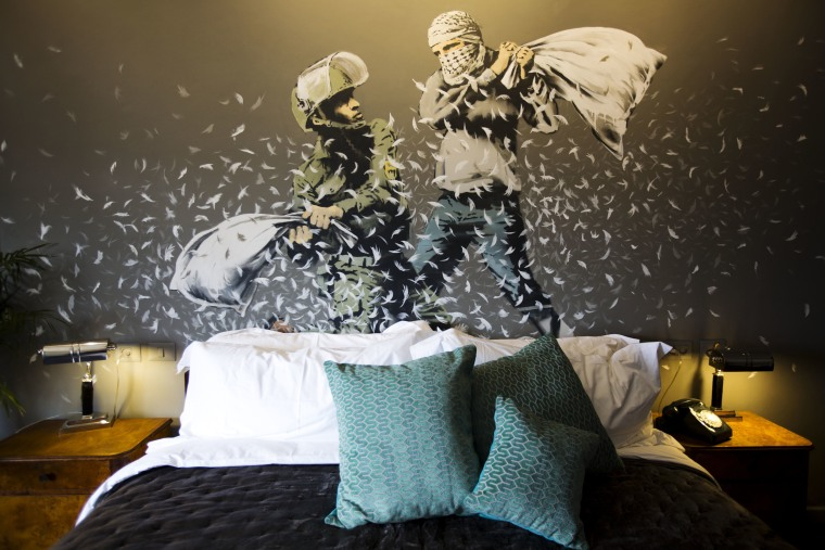"Image: A Banksy wall painting showing Israeli border policeman and Palestinian in a pillow fight is seen in one of the rooms of the ""The Walled Off Hotel."""