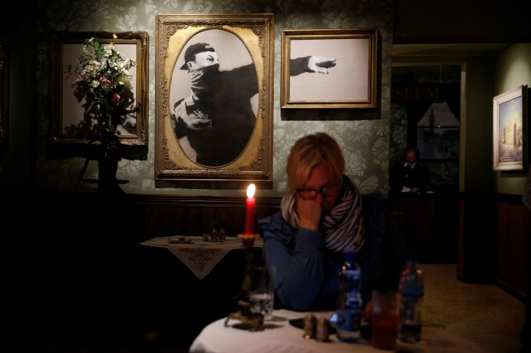 Image: Woman sits in in the Walled Off hotel which was opened by street artist Banksy, in the West Bank city of Bethlehem