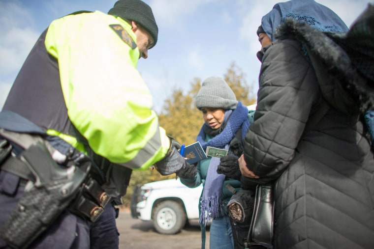 Image: An RCMP officer checks the documents of two women from Sudan after they illegally crossed the Canada-US border near Hemmingford, Quebec, Feb. 26, 2017.