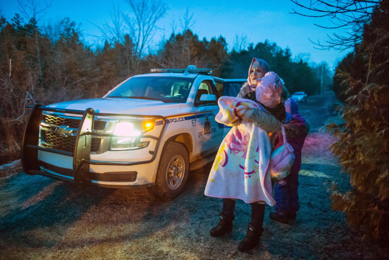 Image: RCMP take members of an extended family of seven people from Turkey into custody after they illegally crossed the U.S.-Canada border just before dawn on Feb. 28.