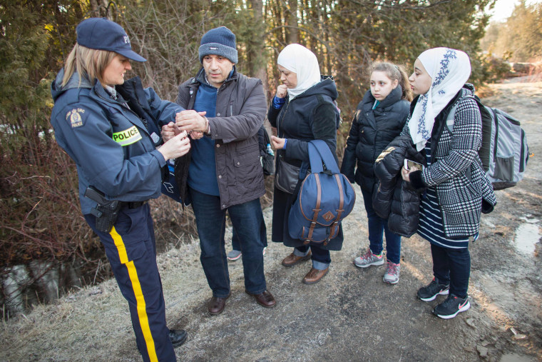 Image: An officer handcuffs a man from Syria after he and his family illegally crossed the U.S.-Canada border, Feb. 27.