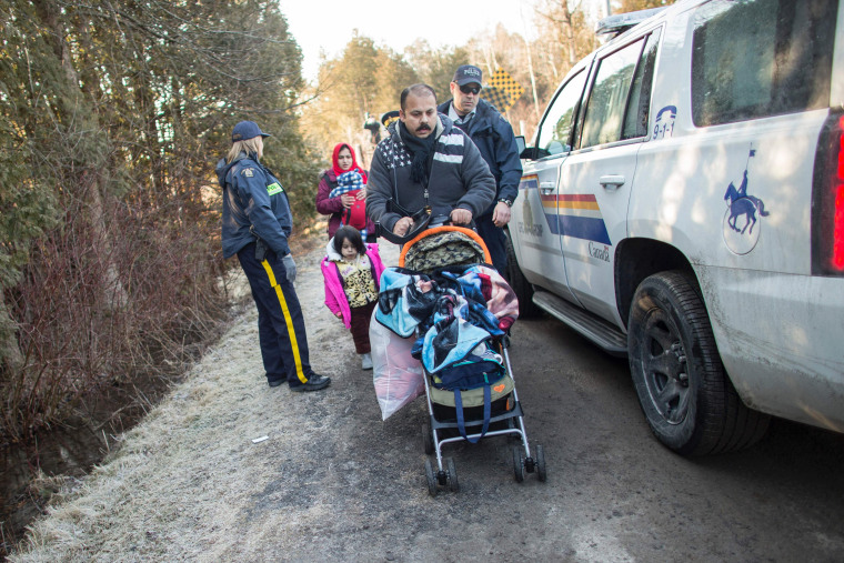 Image: The family is led away by RCMP officers after they illegally crossed the U.S.-Canada border, Feb. 28.