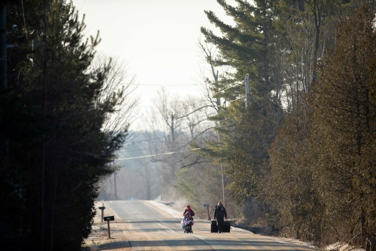 Image: A family of four from Pakistan walk down Roxham Road in Champlain, New York, towards the U.S.-Canada border, Feb. 28.