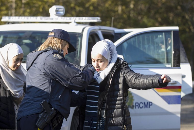 Image: An officer searches the 18 year-old Syrian woman.