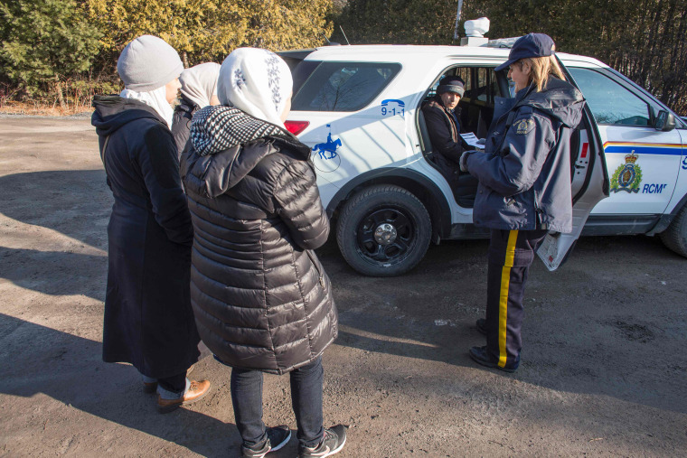 Image: An RCMP officer reads the family from Syria their rights after they were arrested for illegally crossing the border near Hemmingford, Quebec, Feb. 28.