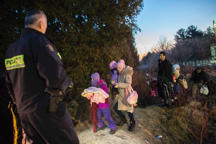 Image: RCMP officers look on as an extended family of seven people from Turkey illegally cross the border just before dawn on Feb. 28.