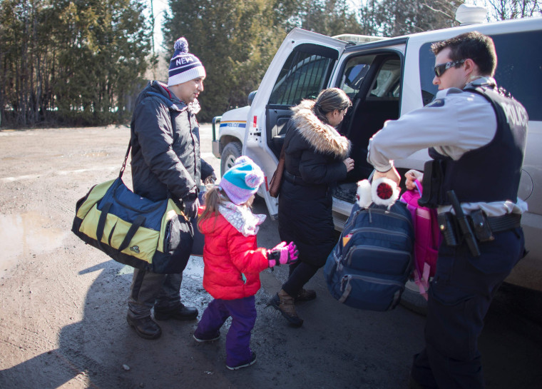 Image: A family from Colombia is arrested by the RCMP after illegally crossing the border.