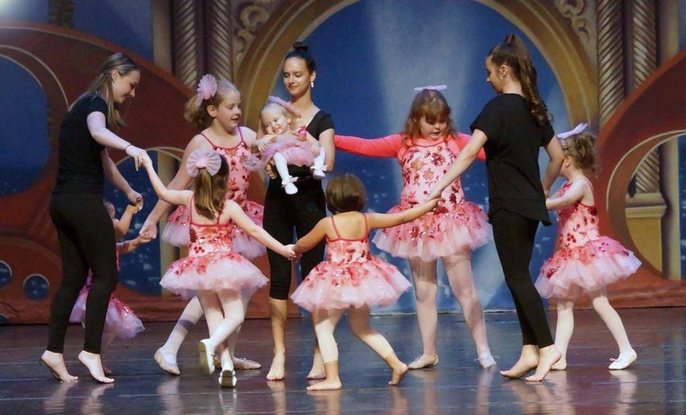 Volunteers help student dancers during A Chance to Dance stage performance