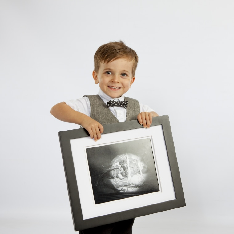 3-year-old Lukas Sheppard holds his baby picture where he spent 93 days in the NICU after he was born in 2013.
