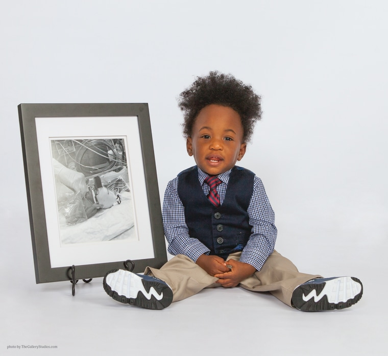 Elijah hunt poses with a picture of himself as an infant in the NICU at St. Joseph's Women's Hospital in Florida in 2015