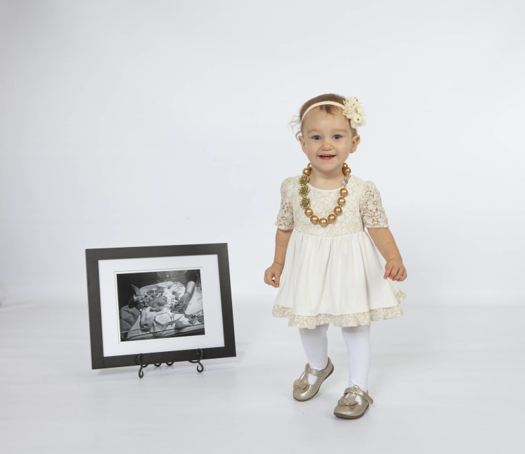 2-year-old Chelsie Harkness poses with her NICU photo for the 2017 High Risk Hope Babies Calendar.