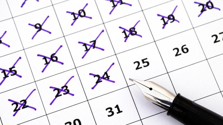 Fountain pen lying on calendar with marking days