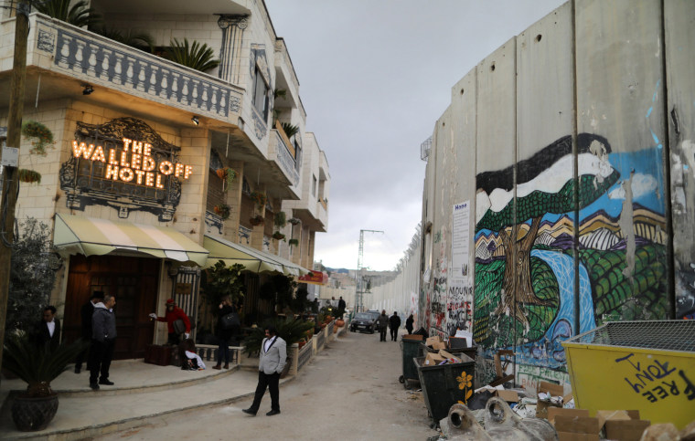 Image: People stand outside the Walled Off hotel, which was opened by street artist Banksy, in the West Bank city of Bethlehem