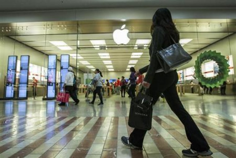 People walk past the Apple Store while shopping at the Los Cerreitos Center mall on Black Friday in Cerritos