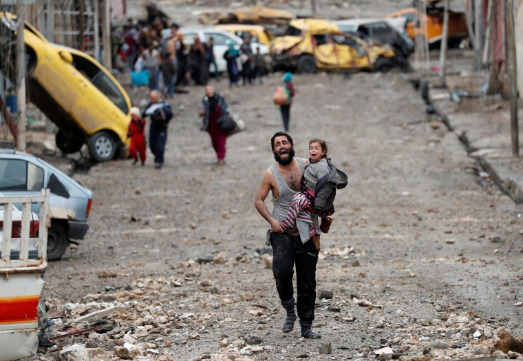 Image: A man cries as he carries his daughter while walking from an Islamic State-controlled part of Mosul towards Iraqi special forces soldiers during a battle in Mosul