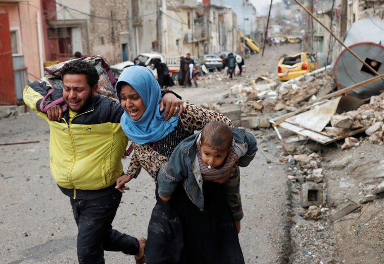 Image: Men and woman cry while carrying a child as they run from Islamic State controlled part of Mosul towards Iraqi special forces soldiers during a battle in Mosul