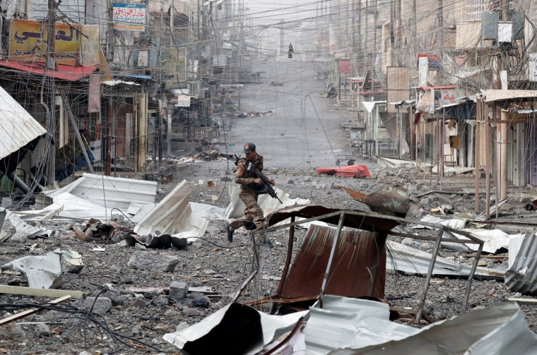 Image: An Iraqi special forces soldier runs across a street during a battle with Islamic State militants in Mosul