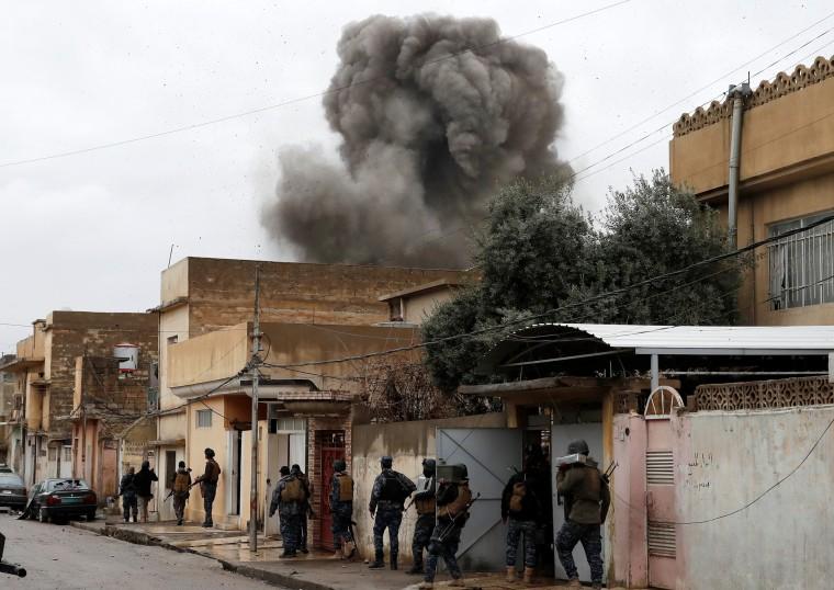 Image: Iraqi policemen walk during an airstrike against Islamic State militants in Mosul