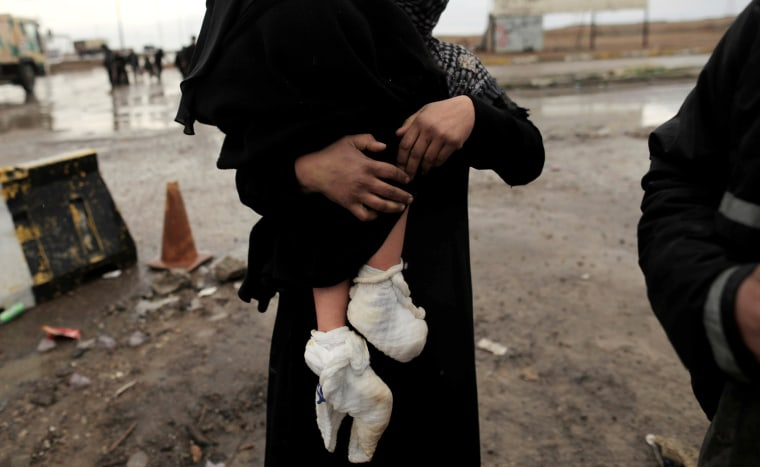 Image: A displaced Iraqi woman carries her injured daughter after fleeing their home, as Iraqi forces battle with Islamic State militants, in western Mosul