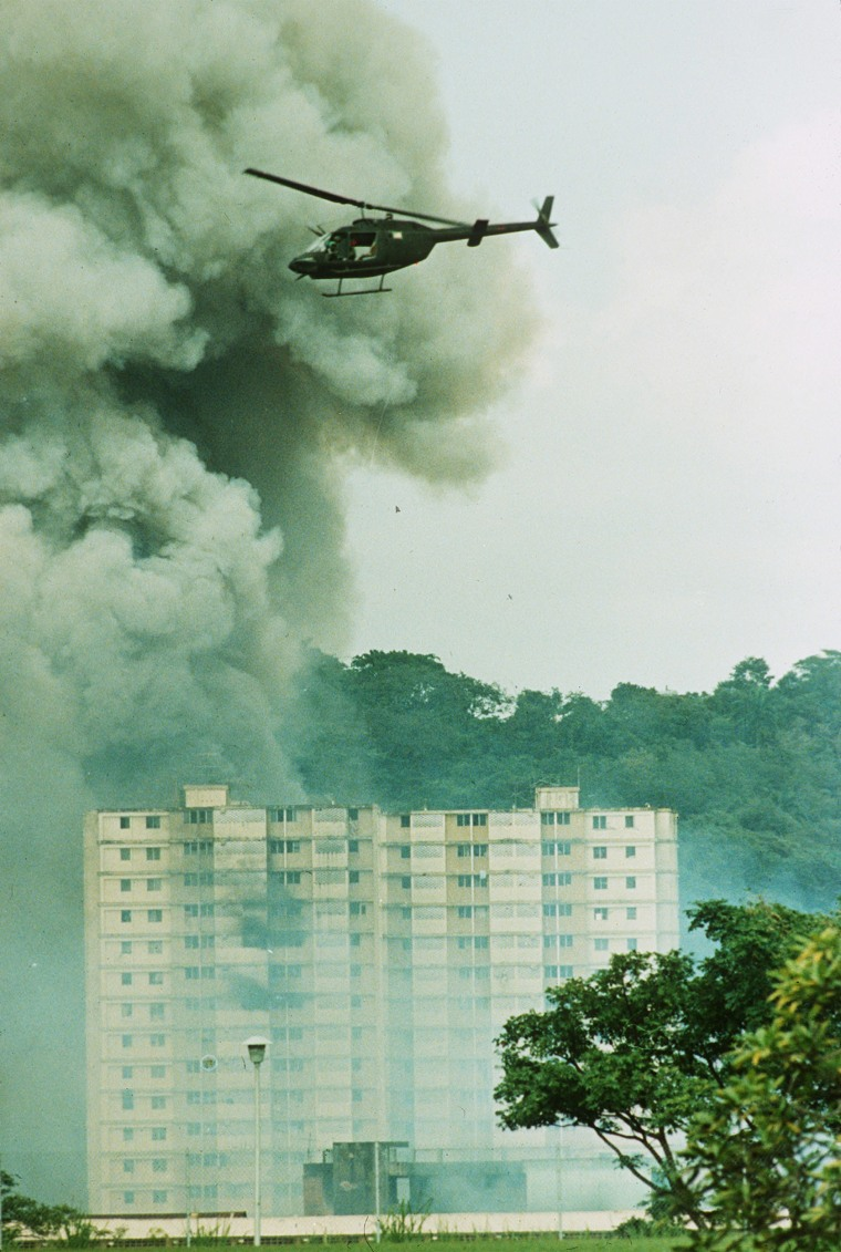 Image: A U.S. military helicopter flies over a burning building near the Pacific Defense Headquarters in Panama City on December 20, 1989