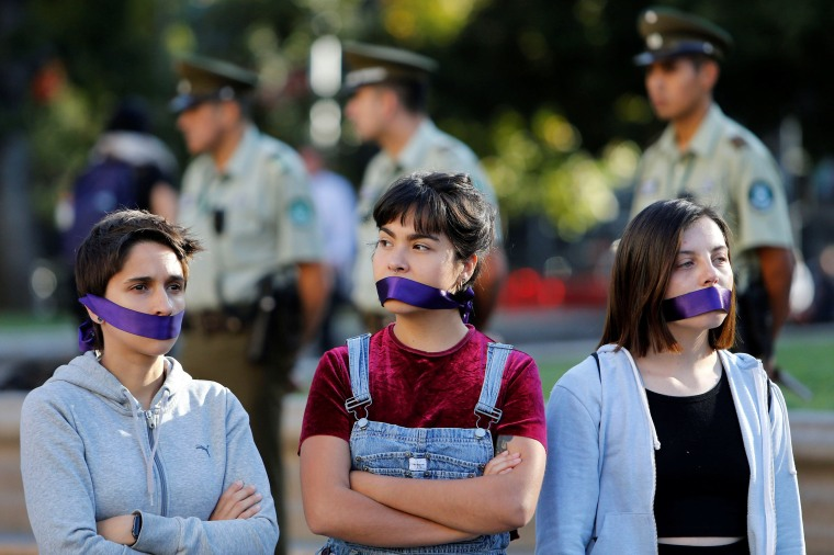 Image: Women cover their mouths as they attend a peaceful demonstration in front of the government house as part of International Women's Day, in Santiago